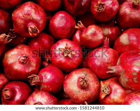 Pomegranate garnet fruit background pattern. Pomegranate whole with flower. Fresh raw organic garnet fruit pile texture background. Ruby natural pomegranate (garnet fruit) heap close up top view. #1581244810