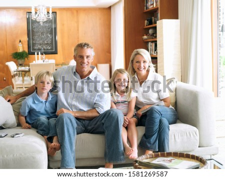 Portrait of happy family on home sofa relaxing and smiling at camera #1581269587