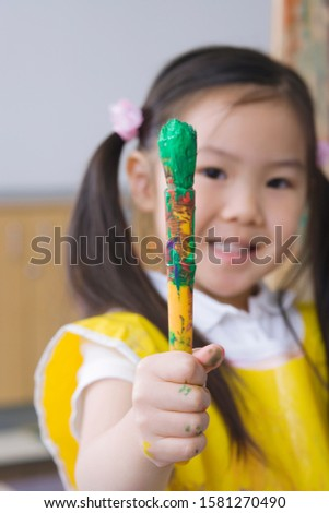 Girl in school art class holding paintbrush at camera smiling at camera #1581270490