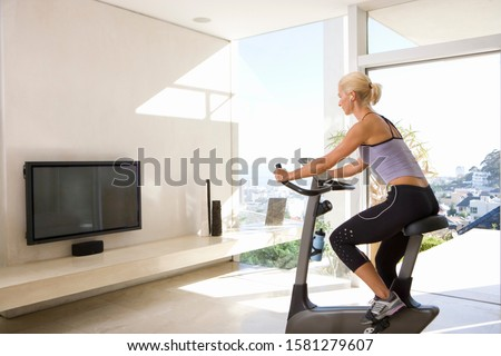Mature woman on exercise bike watching television at home #1581279607