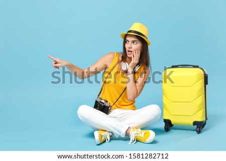 Traveler tourist woman in yellow casual clothes hat with suitcase photo camera isolated on blue background. Female passenger traveling abroad to travel on weekends getaway. Air flight journey concept #1581282712