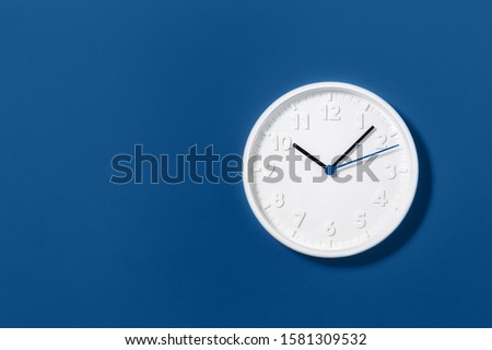 Big white plain wall clock on trending dark blue background. Ten o'clock. Close up with copy space, time management or school concept and summer standard or winter time change, opening hours. #1581309532