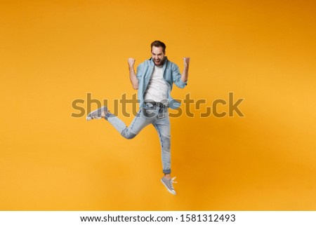 Joyful young bearded man in casual blue shirt posing isolated on yellow orange background, studio portrait. People sincere emotions lifestyle concept. Mock up copy space. Jumping doing winner gesture #1581312493