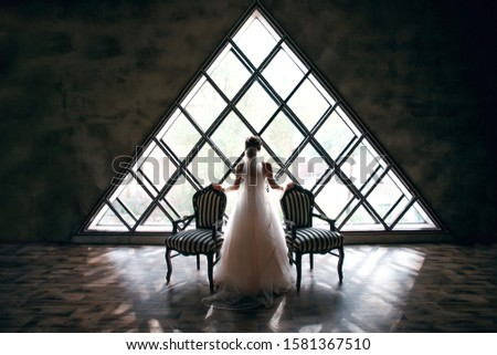 bride in a wedding dress near two striped armchairs, black and white, against a background of a triangular window, an empty attic, stylish look, vintage interior, incredible window, beautiful design #1581367510