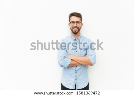 Joyful positive guy posing with arms folded. Handsome young man in casual shirt and glasses standing isolated over white background. Happy man portrait concept #1581369472