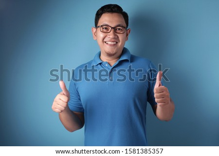 Portrait of funny attractive cute young Asian man in blue shirt smiling and showing thumbs up sign, half body portrait with selective focus #1581385357