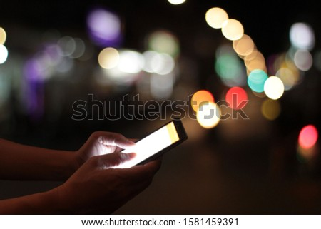 The hand of a man who uses a smartphone in the dark Navigate to the touch screen that shines with his finger, with bokeh and blurry backgrounds. #1581459391