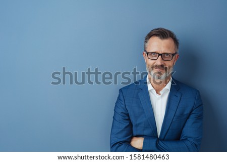 Confident middle-aged man in blue blazer and white shirt, wearing glasses, standing with his arms folded against plain blue background with copy space and looking at camera #1581480463