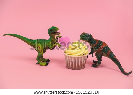 cute green plastic dinosaur toys with cupcakes decorated with pink heart on a pastel pink background