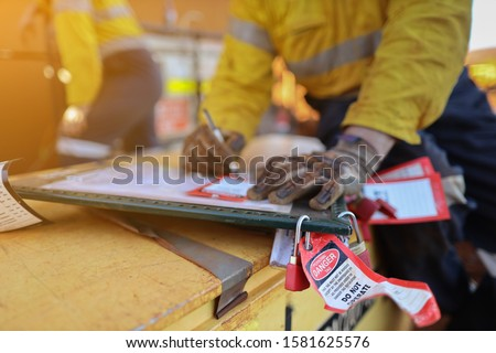 Personnel red danger locks attached with danger tags are locking on safety isolation permit lock box with defocused worker writing name, sign on prior locking on work permit safety control box