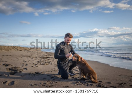 Male runner is having some rest after morning jogging with his dog. He is using phone for a call and taking picture of his furry friends.