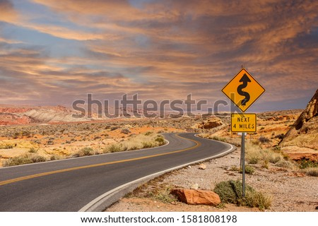 A road sign in the middle of a desert showing curves ahead #1581808198
