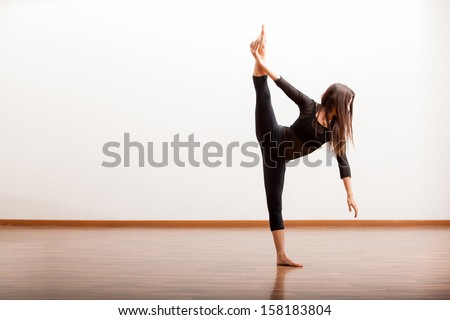 Pretty Hispanic female jazz dancer practicing some dance moves in a dance academy #158183804