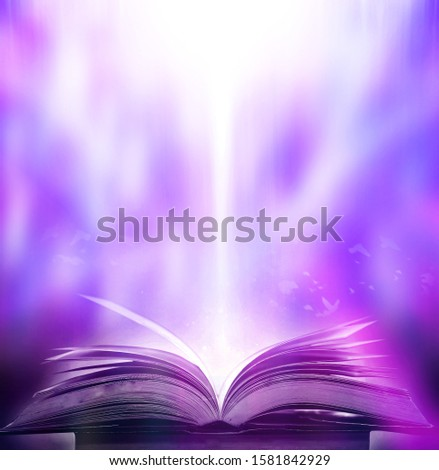 An ancient book that opens with magic, the magic light in the darkness on the wooden table, by the bright light shining down as the power to search for knowledge, religion and background #1581842929