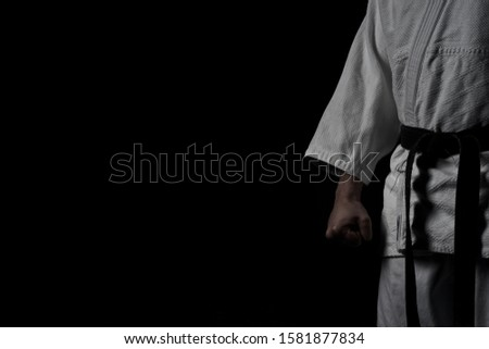 A low key photo of a half man in Aikido uniform with a strong fist keeping a martial arts pose. Royalty-Free Stock Photo #1581877834