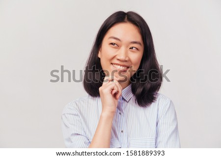 Portrait thoughtful girl touches chin. copyspace at empty place. Businesslike beautiful young woman of Asian appearance dressed in striped office shirt stands isolated white background in Studio. #1581889393