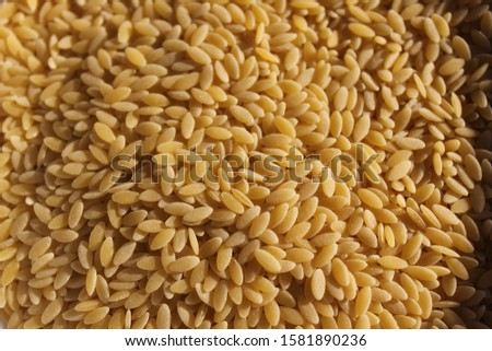 Orzo from Italian for 'barley',  also known as risoni  is a form of short-cut pasta, shaped like a large grain of rice. #1581890236