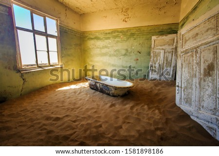 Abandoned and forgotten building and room left by people and being taken over by encroaching sandstorm, Kolmanskop ghost town, Namib Desert Royalty-Free Stock Photo #1581898186