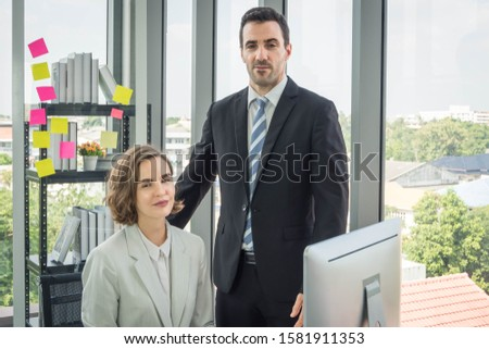 Business men and women Looking at the camera In both of their offices With a tall window in the background Royalty-Free Stock Photo #1581911353