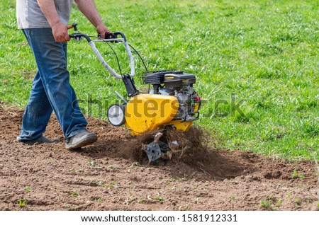 Man Farmer plows the land with a cultivator. Agricultural machinery: cultivator for tillage in the garden,motor cultivator. #1581912331