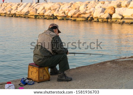 A fisherman waits for the fish to take the bait. Port of Rimini #1581936703