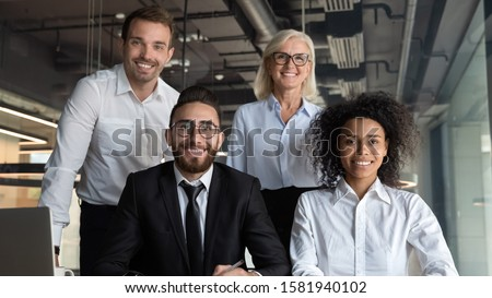 Portrait of smiling multiracial businesspeople marketing department posing at desk in modern office, group picture of happy multiethnic diverse colleagues or coworkers look at camera at workplace #1581940102