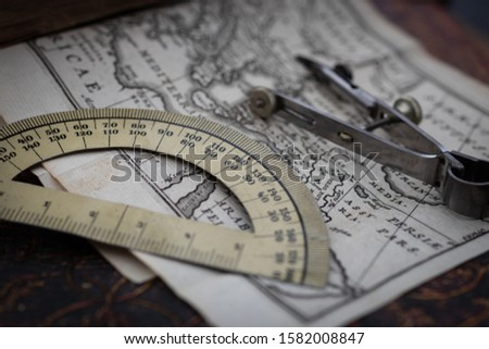 Macro photo of  old vintage Calipers and 180 degrees vintage metall protractor on a map page of the eastern Mediterranean from an authentic 17th century book. Close up, vintage travel concept