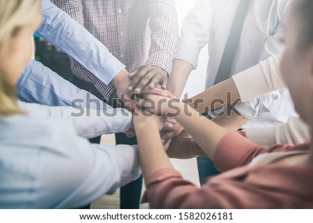 Close up view of young business people putting their hands together. Stack of hands. Unity and teamwork concept. #1582026181