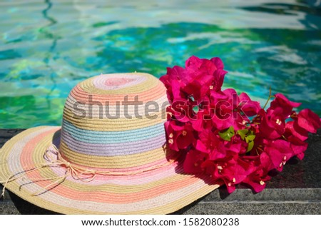 Beautiful hat and flowers at the pool. Sea vacation background. Vacation in the tropics. Holidays in topical countries. #1582080238