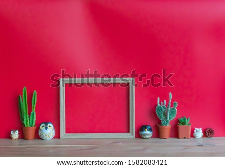 Three  cactus,blank  wooden  picture  frame,simulated  owl  and  pine  cone  on  wood  table  with  red  background,mockup