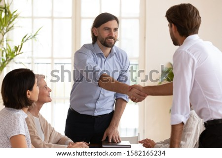Smiling male boss shaking hands with young manager, welcoming new employee in office, introducing to professional team. Pleasant team leader greeting client at brainstorming meeting with coworkers. #1582165234