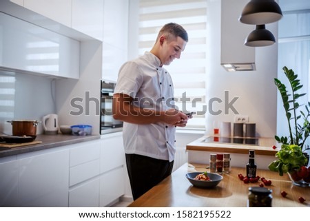 Side view of attractive smiling caucasian chef in uniform taking picture of fresh pasta on plate. Italian cuisine.