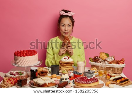 Sweet temptation. Lovely Asian woman enjoys festive gathering, sits at table with many cakes, bites delicious croissant, being sweettooth, licks lips isolated over pink background. Tasting of desserts #1582205956