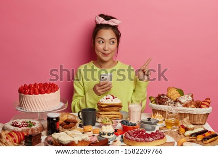 Cheerful glad brunette Asian girl surrounded by biscuits, cookies and cakes, enjoys sweet food during festive time, enjoys holidays treats, points at blank space, uses mobile phone. Cheat meal #1582209766