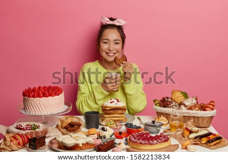 Happy housewife baked many tasty desserts, waits for husband, has delicious breakfast, eats oat cookies with milk, poses indoor. Addicted sweet lover has unhealthy nutrition, smiles toothily #1582213834