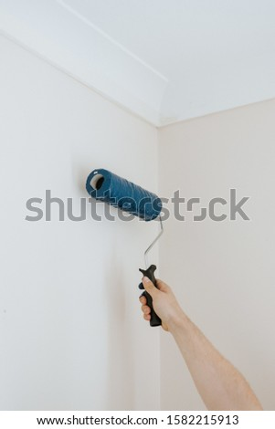 A vertical closeup shot of a person using paint rollers with the color blue #1582215913