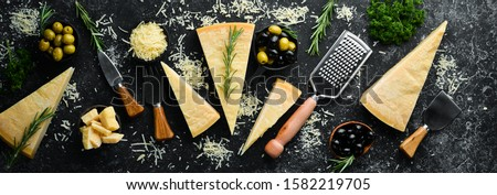 Set of hard cheeses with cheese knives on black stone background. Parmesan. Top view. Free space for your text. Royalty-Free Stock Photo #1582219705