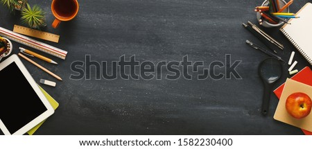 Education background. Supplies for school border on black chalkboard, panorama with empty space