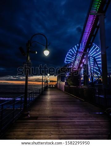 A beautiful vertical shot of an empty bridge near an amusement park during night #1582295950