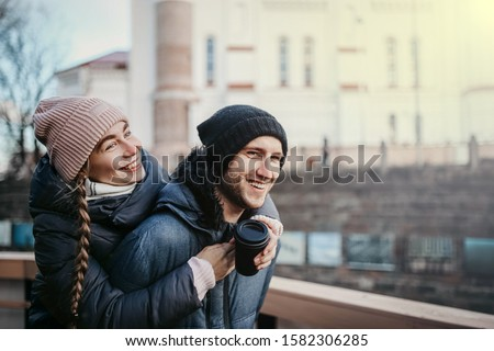 Loving couple in winter clothes and knitted hats walk around the city in the winter before Christmas and New Year.