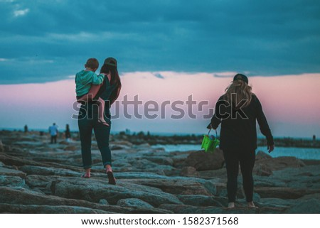 A shot of people standing on a rocky surface near body of water #1582371568