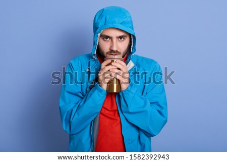 Studio shot of attractive young man with beard, having unhappy facial expression, holding thermo mug with coffee or tea, dresses blue jacket with hood and red shirt, being cold, basking hands. #1582392943