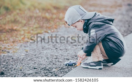 Boy crouches and plays with toy cars on the street. A child dressed in autumn clothes and a baseball cap. Shallow depth of field and slight noise. Horizontal picture.