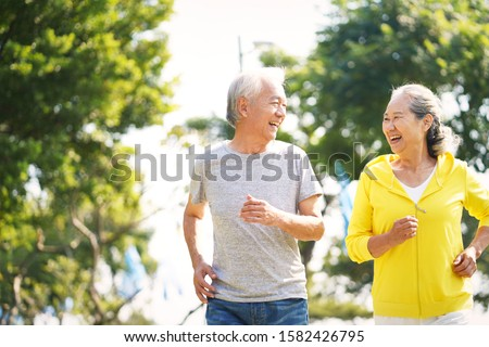 happy asian old couple jogging running outdoors in park Royalty-Free Stock Photo #1582426795