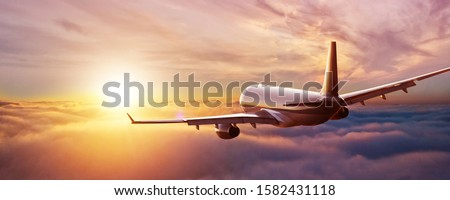 Passengers commercial airplane flying above clouds in sunset light. Concept of fast travel, holidays and business. #1582431118