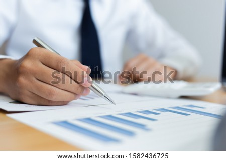 Business men analyze financial data for the company's revenue with graphs and calculators, accounting concept #1582436725