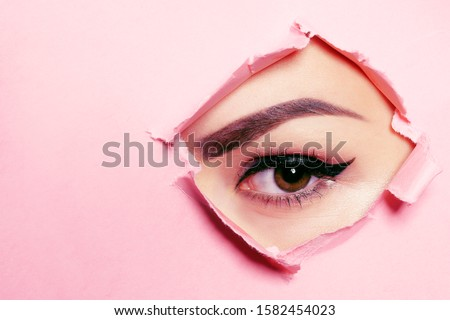 Beautiful brown eye, perfect eyebrows. Beauty salon, eyebrow master, tattoo master shooter and eyebrow. Beautiful eye on a pink background. Royalty-Free Stock Photo #1582454023