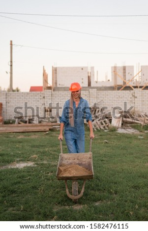 A girl carries a cart on the background of construction #1582476115