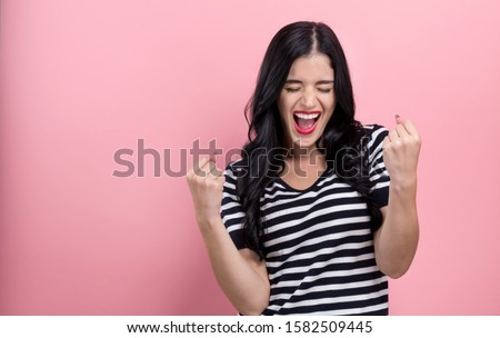Happy young woman making a yay gesture on a pink background #1582509445