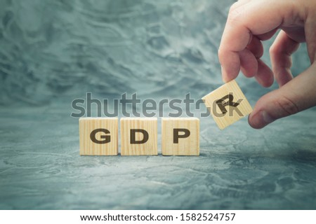 Hand with wood cube block with word GDPR. Concept legal EU protect information general data protection regulation and sign key icon #1582524757